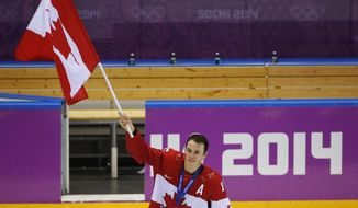 Jonathan Toews of Canada (16) skates with the Canadian flag after the medals ceremony in the men's gold medal ice hockey game at the 2014 Winter Olympics, Sunday, Feb. 23, 2014, in Sochi, Russia. Canada won gold by defeating Sweden 3-0. (AP Photo/Petr David Josek)