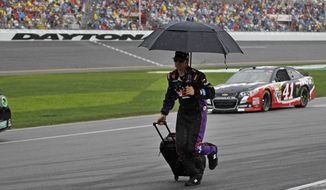 A crew member runs down pit road during a rain delay in the NASCAR Daytona 500 Sprint Cup series auto race at Daytona International Speedway in Daytona Beach, Fla., Sunday, Feb. 23, 2014. (AP Photo/Terry Renna)