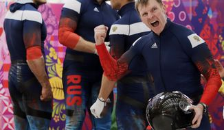 The team from Russia RUS-1, with Alexander Zubkov, foreground, Alexey Negodaylo, Dmitry Trunenkov, and Alexey Voevoda, react after their third run during the men's four-man bobsled competition final at the 2014 Winter Olympics, Sunday, Feb. 23, 2014, in Krasnaya Polyana, Russia. (AP Photo/Jae C. Hong)