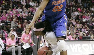 Florida's Kayla Lewis (22) is called for the foul as she tries to block South Carolina's Khadijah Sessions (5) during the second half of their NCAA college basketball game, Sunday, Feb. 23, 2014, in Columbia, SC. South Carolina defeated Florida 69-55. (AP Photo/Mary Ann Chastain)