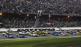 The field takes the green flag after more than a six hour rain delay to restart the NASCAR Daytona 500 Sprint Cup series auto race at Daytona International Speedway in Daytona Beach, Fla., Sunday, Feb. 23, 2014. (AP Photo/Terry Renna)