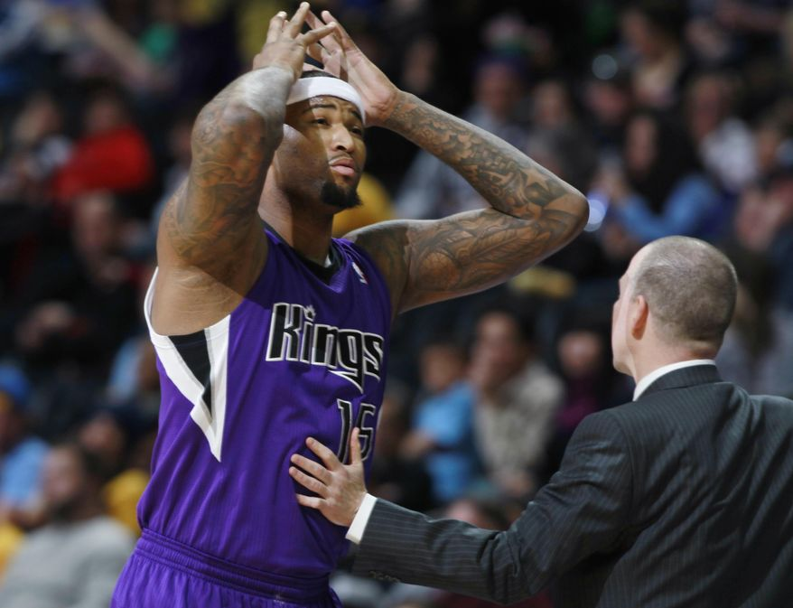 Sacramento Kings center DeMarcus Cousins, left, reacts after being called for his second personal foul as head coach Michael Malone talks to him during an NBA basketball game against the Denver Nuggest in Denver, Sunday, Feb. 23, 2014. (AP Photo/David Zalubowski)