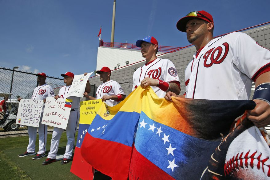 Washington Nationals' Gabriel Alfaro, left, Wilson Ramos, Sandy Leon, Jose Lobaton, and Jhonatan Solano hold flags and signs for reporters after a spring training baseball workout, Sunday, Feb. 23, 2014, in Kissimmiee, Fla. The players are asking for an end to the violence in Venezuela. All the players are from South America. (AP Photo/Alex Brandon)