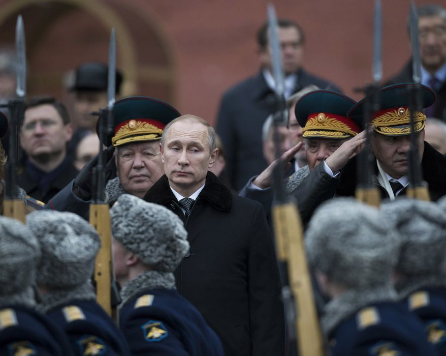 Russian President Vladimir Putin, center, attends a wreath-laying ceremony at the Tomb of the Unknown Soldier in Moscow, Russia, Sunday, Feb. 23, 2014. The Defenders of the Fatherland Day, celebrated in Russia on Feb. 23, honors the nation's military and is a nationwide holiday. (AP Photo/Alexander Zemlianichenko)