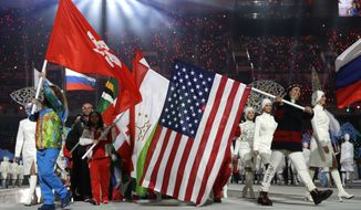 United States' Julie Chu, right, carries the flag during the closing ceremony of the 2014 Winter Olympics, Sunday, Feb. 23, 2014, in Sochi, Russia. (AP Photo/Darron Cummings)