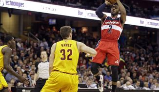Washington Wizards' John Wall (2) shoots over Cleveland Cavaliers' Spencer Hawes (32) in the third quarter of an NBA basketball game, Sunday, Feb. 23, 2014, in Cleveland. Wall scored 21 pouts to lead the Wizards to a 96-83 win. (AP Photo/Mark Duncan)