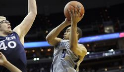 Georgetown guard Markel Starks (5) goes to the basket against Xavier center Matt Stainbrook (40) during the second half of an NCAA college basketball game, Saturday, Feb. 22, 2014, in Washington. Georgetown won 74-52. (AP Photo/Nick Wass)
