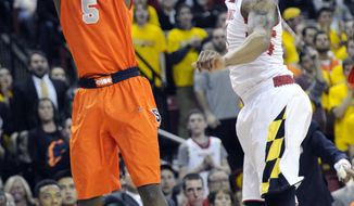 Syracuse forward C.J. Fair (5) shoots against Maryland guard Nick Faust, right, during the first half of an NCAA college basketball game, Monday, Feb. 24, 2014, in College Park, Md. (AP Photo/Nick Wass)
