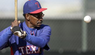 Texas Rangers manager Ron Washington prepares to hit a ball as he works out infielders during spring training baseball practice, Sunday, Feb. 23, 2014, in Surprise, Ariz. (AP Photo/Tony Gutierrez)