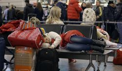 A passenger sleeps while waiting for a flight at the Sochi Airport following the 2014 Winter Olympics, Monday, Feb. 24, 2014, in Sochi, Russia. (AP Photo/Darron Cummings)