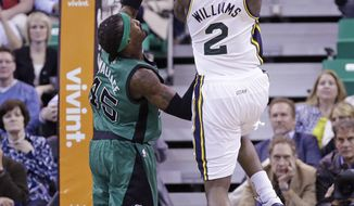 Utah Jazz's Marvin Williams (2) shoots as Boston Celtics' Gerald Wallace (45) defends in the second quarter of an NBA basketball game, Monday, Feb. 24, 2014, in Salt Lake City. (AP Photo/Rick Bowmer)