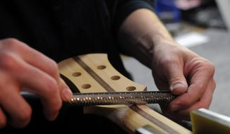 FOR RELEASE FOR SATURDAY, MARCH 1, 2014, AT 12:01 A.M., CST - In this Feb. 6, 2014 photo, John Brown shapes a maple guitar neck with wenge and lace wood laminate at his shop, Brown's Guitar Factory, in Inver Grove Heights, Minn. (AP Photo/Pioneer Press, Scott Takushi) MINNEAPOLIS STAR TRIBUNE OUT.