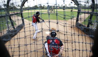 Atlanta Braves center fielder B.J. Upton (2) swings at a pitch with Evan Gattis (24) catching, during a spring training baseball workout, Monday, Feb. 24, 2014, in Kissimmee, Fla. (AP Photo/Alex Brandon)