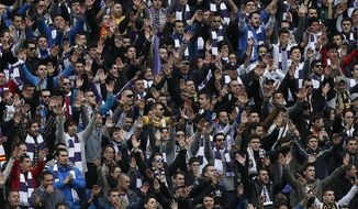 Real Madrid's fans sing during a Spanish La Liga soccer match between Real Madrid and Elche at the Santiago Bernabeu stadium in Madrid, Spain, Saturday, Feb. 22, 2014. (AP Photo/Andres Kudacki)