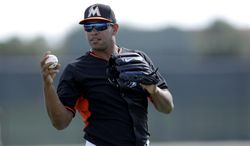 Miami Marlins pitcher Carlos Marmol warms up at the start of a spring training baseball practice Monday, Feb. 24, 2014, in Jupiter, Fla. (AP Photo/Jeff Roberson)