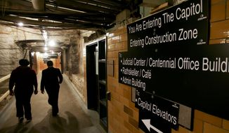 Visitors to the Minnesota State Capitol on  Monday, Feb. 24, 2014, walk through the tunnel system in the basement where new signs point the way for lawmakers and the public who will be navigating a maze of construction when the 2014 legislative session convenes Tuesday in St. Paul, Minn. Crews are charging ahead with a $272 million renovation of the century-old building. For now, the major work is in the basement but will move floor-by-floor until expected completion in 2017. (AP Photo/Jim Mone)
