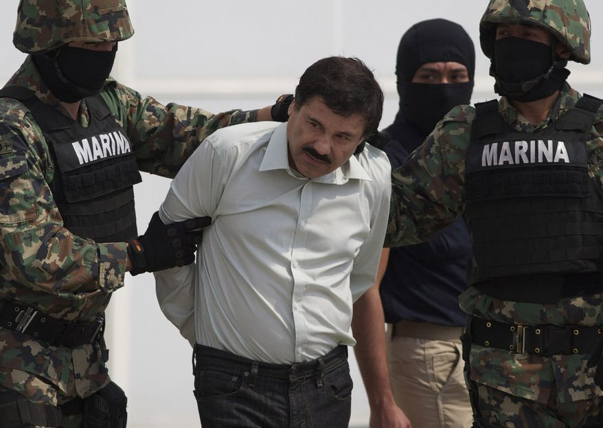 """In this Saturday, Feb. 22, 2014 photo, Joaquin """"El Chapo"""" Guzman is escorted to a helicopter in handcuffs by Mexican navy marines at a navy hanger in Mexico City, Mexico. Guzman, the head of Mexico's Sinaloa Cartel, was captured overnight in the beach resort town of Mazatlan. (AP Photo/Eduardo Verdugo)"""