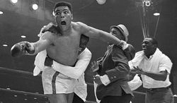 Cassius Clay's handlers hold him back as he reacts after he is announced the new heavyweight champion of the world on a seventh round technical knockout against Sonny Liston at Convention Hall in Miami Beach, Fla., on Feb. 25, 1964.  (AP Photo)