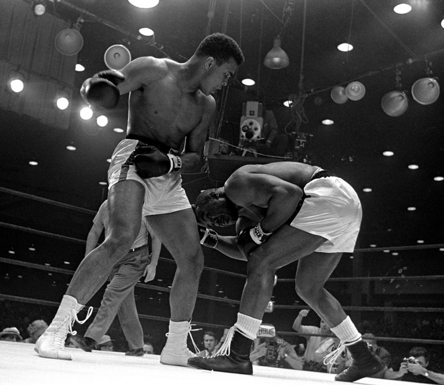 Sonny Liston, right, ducks low and weaves to escape a punch from Cassius Clay's cocked right fist during the 5th round of the heavyweight title fight in Miami Beach, Florida, February 25, 1964.  Clay won on a seventh round technical knockout. (AP Photo/stf)