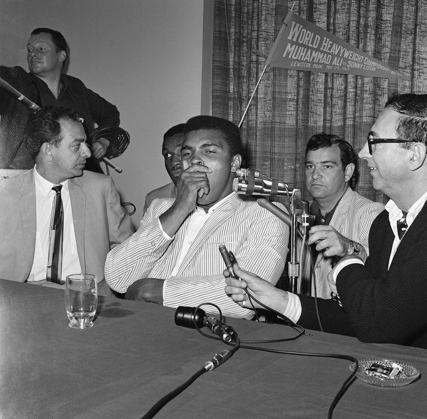 Heavyweight boxing champion Muhammad Ali (Cassius Clay) covered his yawn as he faced newsmen after arrival at his motel in Auburn nearby in Lewiston, Me. on May 24 1965.   He and his entourage had driven up from his Chicopee Falls, Mass. training camp.   He puts his title on the line against Sonny Liston. (AP Photo)