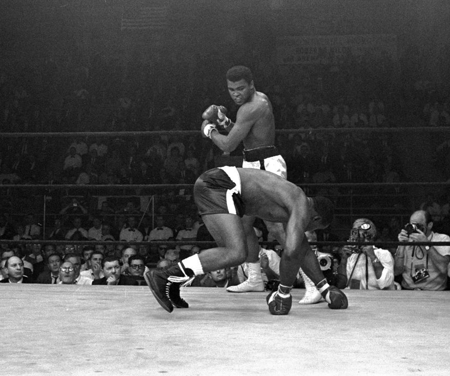 Muhammad Ali peers down at challenger Sonny Liston as Liston goes down in the first and only round of their title bout in Lewiston, Maine, May 25, 1965.  Ali won on a KO to retain his crown.  (AP Photo/stf)
