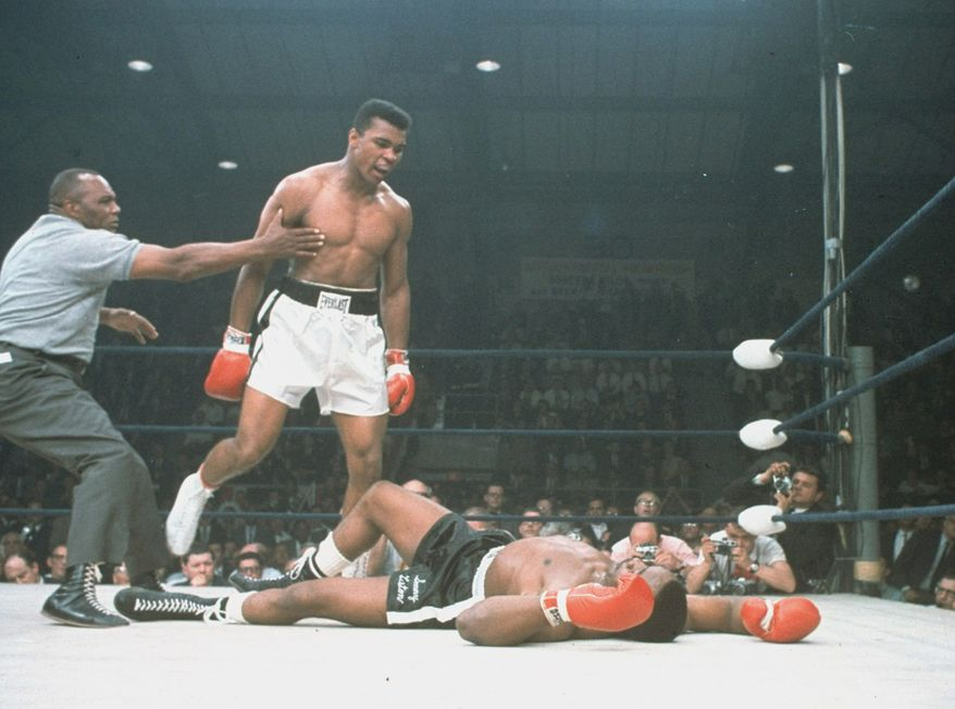 World heavyweight champion Muhammad Ali is held back by referee Joe Walcott after Ali knocked out challenger Sonny Liston in 1 minute, 42 seconds of the first round of the scheduled 15 round championship bout in Lewiston, Maine, May 25, 1965.  (AP Photo/stf)