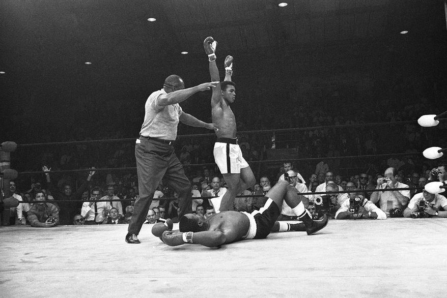 Heavyweight champion Muhammad Ali (Cassius Clay) , arms upraised, begins his victory dance around challenger Sonny Liston on May 25, 1965 after he cut short their scheduled 15-round title bout by knocking him out in one minute of the first round.  Referee Joe Walcott waves his arm ending the bout. (AP Photo)