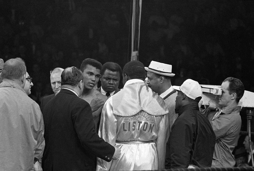 Heavyweight champion Muhammad Ali ?Cassius Clay? (left) loses smile and raises hand briefly during exchange with Sonny Liston after weight-in ceremony at Lewiston, Me., arena on May 25, 1965. The exchange never went beyond words and the action will be a 15-round title bout. In center is Drew Brown, an Ali  trainer. Clay weighed 206 and Liston 215 ¼. (AP Photo)