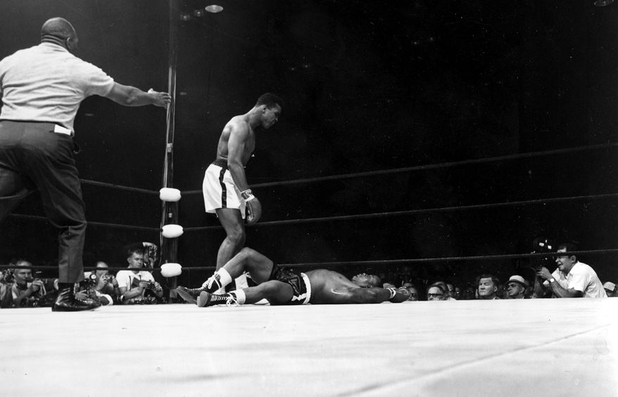 Heavyweight champion Muhammad Ali stands over challenger Sonny Liston, who lies stretched on the canvas, in first and only round of the scheduled 15-round title bout in Lewiston, Maine, on May 25, 1965.  Ali won on a KO.  The referee is Joe Walcott.  (AP Photo)