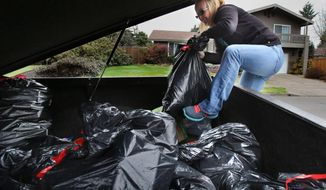 In this photo from Feb. 22, 2014, Oregon State senior Stephanie Lilly, of Harrisburg, Ore., organizes bags of cans in the back of her mother's pickup truck while collecting in northeast Eugene, Ore. Lilly has paid for much of her college education by collecting cans and bottles. She graduates this spring. (AP Photo/The Register-Guard, Brian Davies)