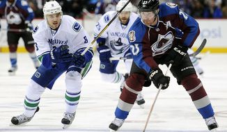 FILE - In this March 24, 2013, file photo, Vancouver Canucks defenseman Chris Tanev, left, defends Colorado Avalanche right wing Milan Hejduk, right, of Czech Republic, in an NHL hockey game in Denver. Hejduk, 38, is retiring from the NHL after 14 seasons, all with the Avalanche. (AP Photo/Chris Schneider, File)