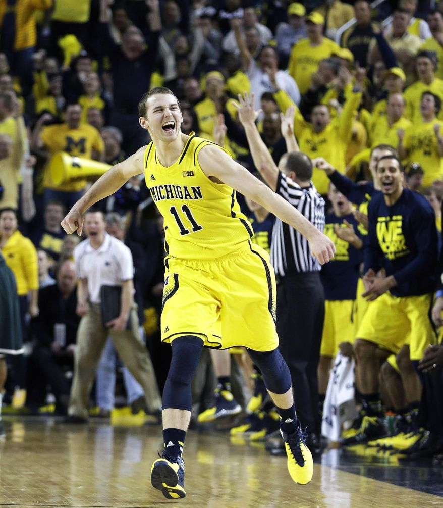 Michigan guard Nik Stauskas (11) reacts after making a three point basket during the second half of an NCAA college basketball game against Michigan State, Sunday, Feb. 23, 2014, in Ann Arbor, Mich. Michigan defeated Michigan State 79-70. (AP Photo/Carlos Osorio)