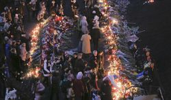 People lay flowers and lit candles at one of the barricades heading to Independence Square,Kiev, the epicenter of the country's recent unrest, on a mourning day Monday, Feb. 24, 2014. Ukraine's acting government issued a warrant Monday for the arrest of President Viktor Yanukovych, last reportedly seen in the pro-Russian Black Sea peninsula of Crimea, accusing him of mass crimes against protesters who stood up for months against his rule. (AP Photo/Efrem Lukatsky)