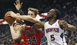 Atlanta Hawks small forward DeMarre Carroll (5) and Chicago Bulls small forward Mike Dunleavy (34) fight for a rebound in the first half of an NBA basketball game  Tuesday, Feb. 25, 2014, in Atlanta. (AP Photo/John Bazemore)