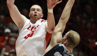 New Mexico's Alex Kirk shoots over with Utah State's Jordan Stone, (25) and defender Spencer Butterfield, bottom right, during the first half of an NCAA college basketball game, Tuesday, Feb. 25, 2014 in Albuquerque, N.M. (AP Photo/Craig Fritz)