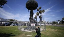 "FILE - In this July 10, 2012, file photo, a photographer takes a picture of ""Chain Reaction,"" a sculpture by Pulitzer Prize-winning cartoonist Paul Conrad, that is displayed  in front of the Civic Center in Santa Monica, Calif. After years of erosion by the ocean's salt air, ""Chain Reaction"" is not in danger of exploding, but of falling down.  The City Council is scheduled to vote late Tuesday Feb. 25, 2014, on whether to move ahead with plans to restore the aging, three-story work. (AP Photo/Jae C. Hong, File)"