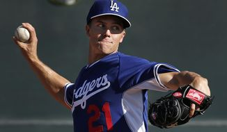 """FILE - In this Monday, Feb. 10, 2014 file photo, Los Angeles Dodgers pitcher Zack Greinke throws during spring training baseball practice  in Glendale, Ariz. It wouldn't bother Zack Greinke if he didn't have to travel for the Los Angeles Dodgers; opener against Arizona in Australia. """"I would say there is absolutely zero excitement about it,"""" was quoted as saying in a story by ESPNLosAngeles.com last weekend. """"There just isn't any excitement to it. I can't think of one reason to be excited for it.""""  (AP Photo/Paul Sancya, File)"""