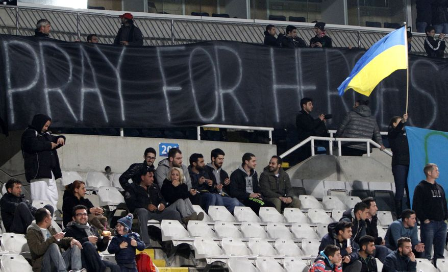 """Fans of Dynamo Kiev hold a banner that reads """"Pray for heroes"""" in honor of victims of violent clashes in the Ukrainian capital, before the start of their Europa League round of 32 first leg match at GSP stadium in Nicosia, Cyprus, Thursday, Feb. 20, 2014. UEFA has moved the Dynamo Kiev vs. Valencia Europa League round of 32 opener to Cyprus, after anti-government clashes in the Ukrainian capital left at least 50 people dead and hundreds injured. (AP Photo/Petros Karadjias)"""