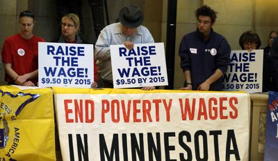 Demonstrators rally at the state Capitol, calling for lawmakers to raise the minimum wage, as the 2014 Minnesota Legislature convened, Tuesday, Feb. 25, 2014, in St. Paul, Minn. (AP Photo/Jim Mone)