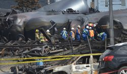 FILE - In this July 6, 2013 file-pool photo, emergency workers examine the aftermath of a train derailment and fire in Lac-Megantic, Quebec. Federal regulators issued an emergency order Tuesday requiring tests of crude oil before shipment by rail to determine how susceptible it is to explosion or fire, a response to a string of train accidents since last summer involving oil from the Bakken region of North Dakota and Montana. A runaway train with 72 tank cars of Bakken oil derailed, exploded and burned in the downtown area of Lac-Megantic, Quebec, near the Maine border in July. Forty-seven people were killed and 30 buildings destroyed. Oil trains have also exploded and burned in North Dakota and Alabama in recent months. (AP Photo/Ryan Remiorz, File-Pool)
