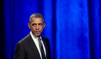President Barack Obama glances at the crowd as walks off the stage after speaking at the National Organizing Summit in Washington, Tuesday, Feb. 25, 2014. (AP Photo/Manuel Balce Ceneta)