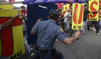 Demonstrators clash with police on their way closer to U.S. Embassy in Manila, Philippines, Tuesday, Feb. 25, 2014 to protest the forthcoming visit of U.S. President Barack Obama. The protesters were also calling for the pullout of U.S. troops in the country under the Visiting Forces Agreement or VFA. (AP Photo/Bullit Marquez)