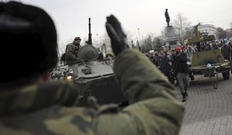 A Russian Army officer, back to camera, helps an armored personnel carrier drive on a street in Sevastopol, Ukraine's Black Sea Port that hosts a major Russian navy base Tuesday, Feb. 25, 2014. Tensions were building up in the Crimea, where ethnic Russians who make the majority of the local population are deeply suspicious of the new Ukrainian authorities who replaced fugitive Russia-backed President Viktor Yanukovych. (AP Photo/Andrew Lubimov)