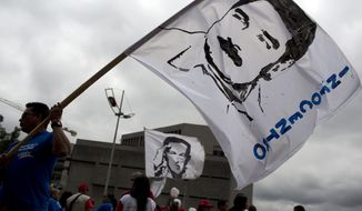 A worker of the National Telecommunications Company, CANTV, holds a banner with a line drawing of Venezuela's President Nicolas Maduro during a pro-government rally in Caracas, Venezuela, Tuesday, Feb. 25, 2014. The acronym INFOCENTRO running along the side banner represents a government program that provides internet services free of charge. (AP Photo/Rodrigo Abd)