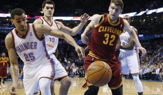 Oklahoma City Thunder guard Thabo Sefolosha (25) and Cleveland Cavaliers center Spencer Hawes (32) watch a loose ball during the second quarter of an NBA basketball game in Oklahoma City, Wednesday, Feb. 26, 2014. Cleveland won 114-104. (AP Photo/Sue Ogrocki)