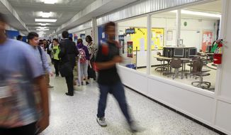 FOR RELEASE SUNDAY, MARCH 2, 2014, AT 12:01 A.M. CST. - In this photo from Feb. 20, 2014, students walk through the hall at the Energy Institute High School in Houston. All the classrooms have a wall of windows as part of an open concept. (AP Photo/Houston Chronicle, Melissa Phillip)