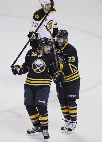 Buffalo Sabres' Matt Moulson (26) celebrates with teammate Ville Leino (23) after scoring the game-tying goal against the Boston Bruins during the third period of an NHL hockey game in Buffalo, N.Y., Wednesday, Feb. 26,  2014. Buffalo won in overtime 5-4.  (AP Photo/Gary Wiepert)