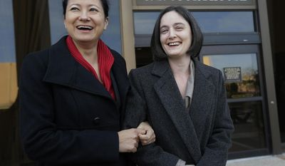 Cleopatra De Leon, left, and partner, Nicole Dimetman, right, arrive at the U.S. Federal Courthouse, Wednesday,  Feb. 12, 2014, in San Antonio, where a federal judge is expected to hear arguments in a lawsuit challenging Texas' ban on same-sex marriage. (AP Photo/Eric Gay)