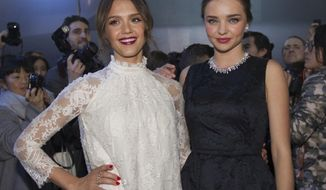 Jessica Alba, left and Miranda Kerr pose prior to the show of H&M's  ready-to-wear fall/winter 2014-2015 fashion collection presented in Paris, Wednesday, Feb. 26, 2014. (AP Photo/Jacques Brinon)
