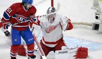 Montreal Canadiens center David Desharnais (51) is stopped by Detroit Red Wings goalie Jimmy Howard (35) during the second period of an NHL hockey game Wednesday, Feb. 26, 2014, in Montreal. (AP Photo/The Canadian Press, Ryan Remiorz)